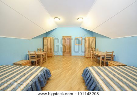 Empty room with two beds and wooden furniture