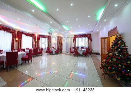 Empty banquet hall with served tables, red chairs, drapes and Christmas tree