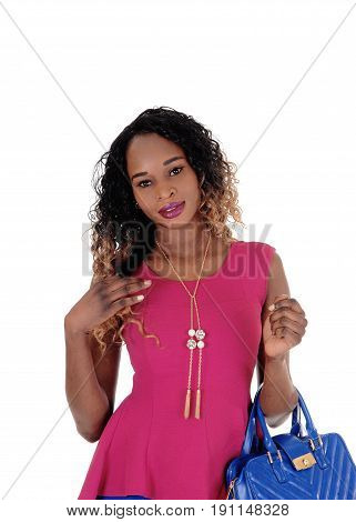 A beautiful young African American woman holding her blue purse and a dark pink blouse standing isolated for white background.