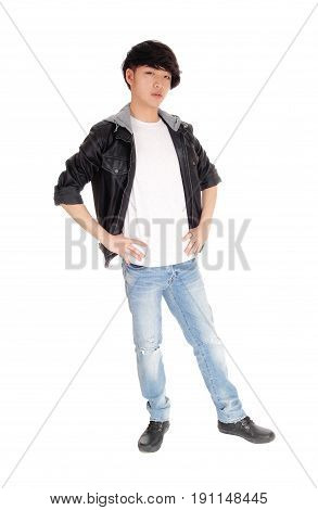 A happy Asian teenager standing in an black jacket holding his hand on his hips isolated for white background.