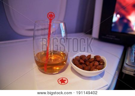 TORONTO, CANADA - JAN 28th, 2017: Air Canada Business class in a passenger plane. A glass of whisky and some warm nuts on a folding table inside a Boeing 777-300ER from AC.