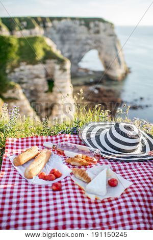 Picnic with french food on the checkered tablecloth on the beautiful rocky coastline background