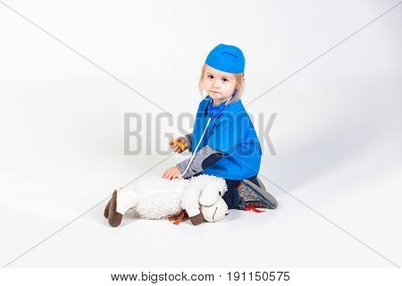 doctor child. small boy in blue uniform playing vet with toy animal of donkey in medical hospital isolated on white background medicine and healthcare copy space
