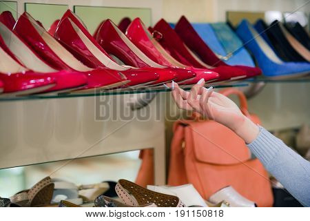 shop assistant hand at shopping showcase with female footwear or colorful shoes and customer beauty and fashion