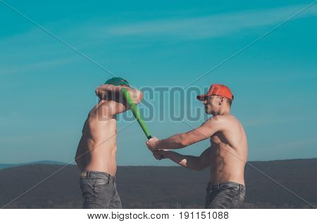 men strong athletes in green and red caps and jeans with naked fit torsos fighting with baseball bat on blue sky on mountain landscape. Conflict and competition. Power success