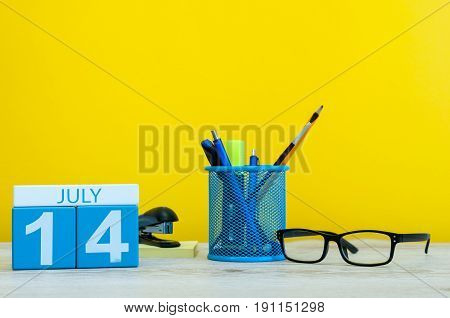 July 14th. Image of july 14, calendar on yellow background with office supplies. Summer time. With empty space for text.