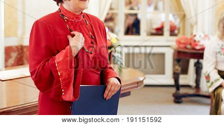 Old Woman Ceremony Master Perfoming Speech In Red Dress  At Wedding Ceremony Reception