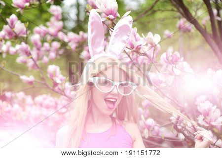 happy girl. Surprised woman or pretty girl with funny glasses bunny ears and open mouth with long blond hair at blossoming tree with magnolia flowers in park on sunny day on floral environment. Easter. Spring