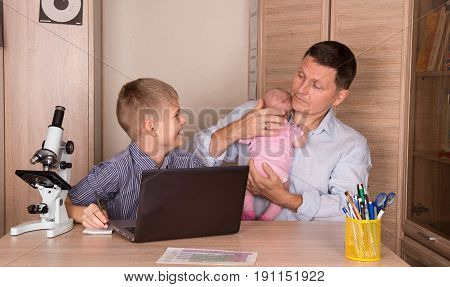 Family lifestyle concept. Smiling boy doing homework using laptop. Father with a newborn baby in his hands helping his laughing son with homework.