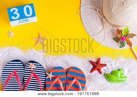 June 30th. Image of june 30 calendar on yellow sandy background with summer beach, traveler outfit and accessories. Summertime concept.