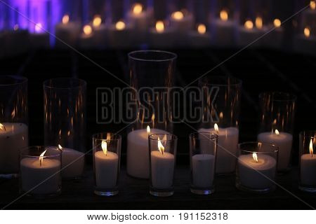 Burning candles of granulated white wax in elegant glass candleholders with flame reflection on dark wooden board on blurred background. Home decor. Holidays celebration. Heat energy