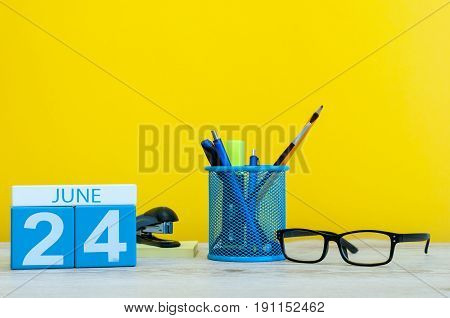 June 24th. Day 24 of month, calendar on yellow background with office supplies. Summer time at work.