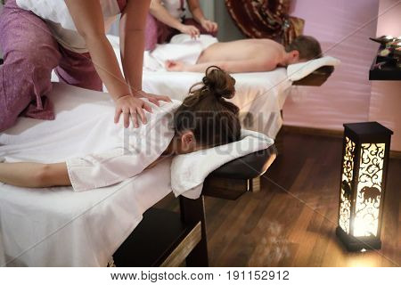 Masseur doing massage on woman body in front of man and other masseur in the spa salon