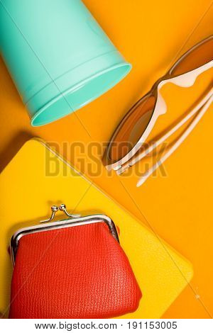 Sunglasses , purse , notebook and  cup on the yellow background top view vertical