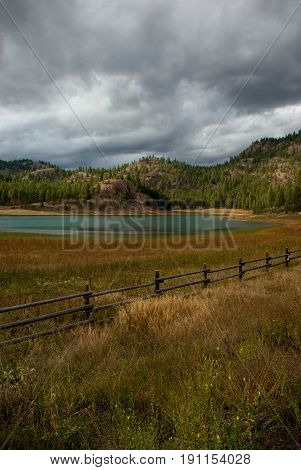 Forboding storm clouds roll over a small lake in the foothills of the Okanagan Valley in British Columbia