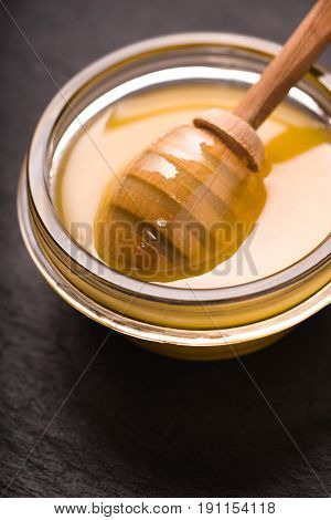 Honey on the glass bowl  with dipper on the dark background vertical