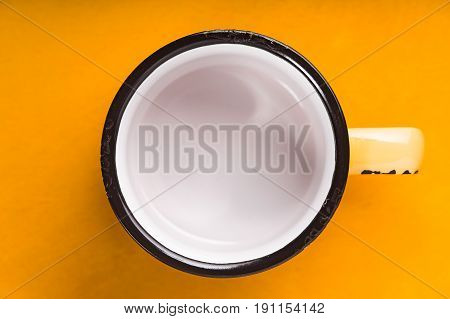 Empty enameled cup on the yellow background top view horizontal