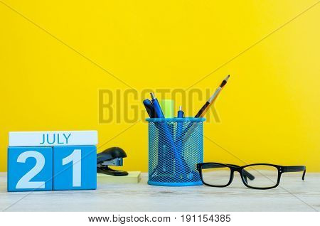 July 21st. Image of july 21, calendar on yellow background with office supplies. Summer time. With empty space for text.