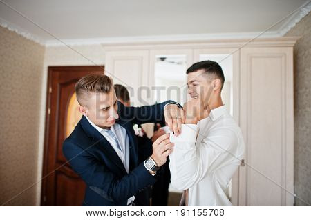 Groomsmen Helping Groom To Dress Up And Get Ready For His Wedding In A Room.