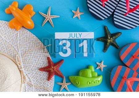July 31st. Image of july 31 calendar with summer beach accessories and traveler outfit on background. Summer day, Vacation concept.