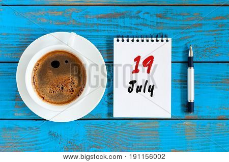 July 19th. Day 19 of month, calendar on blue wooden table background with morning coffee cup. Summer concept.