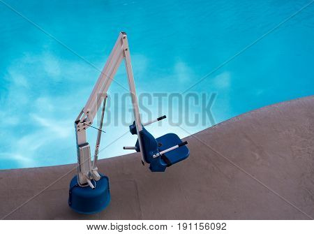 Disabled person pool lift or hoist meets ADA standards installed by swimming pool to lower people into water