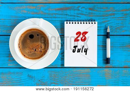 July 28th. Day 28 of month, calendar on blue wooden table background with morning coffee cup. Summer concept.