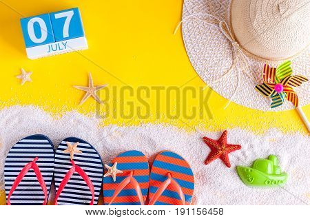July 7th. Image of july 7 calendar with summer beach accessories and traveler outfit on background. Summer day, Vacation concept.