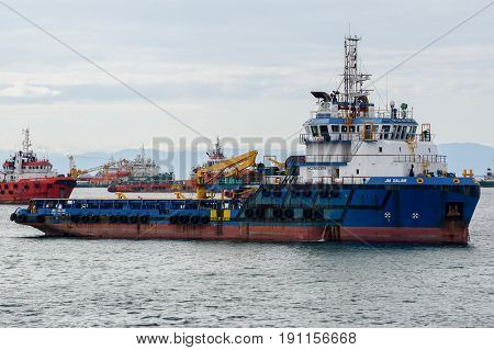 Labuan,Malaysia-July 15,2016:Tug boats pulling out the container ship in Labuan island,Malaysia.Its a sheltered deep water harbour which is an important transshipment point for Brunei Darussalam,Sarawak & Sabah