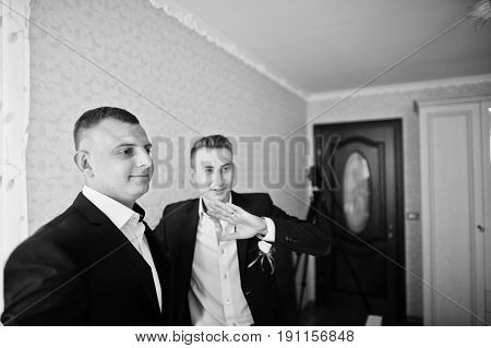 Groomsman And Best Man Or Groomsmen Standing In A Groom's Room. Black And White Photo.
