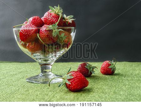 Fresh juicy strawberries in glass bowl. Rustic background with homespun napkin.