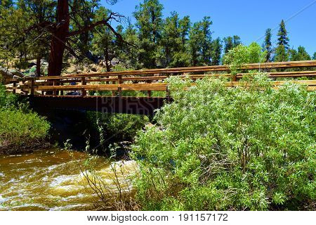 Pedestrian wooden bridge taken over the South Fork of the Kern River on the PCT Hiking Trail in the Sierra Nevada Mountains, CA