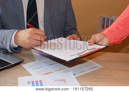 Businessman is signing a contract business contract details. Conceptual image of a man signing a last will and testament document. Colleagues working together in office