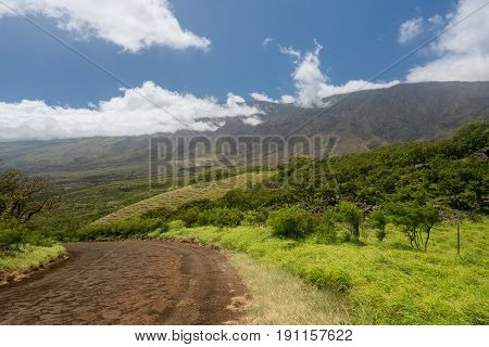 Lonely and remote road past Hana around south of Maui with Haleakala mountain in background