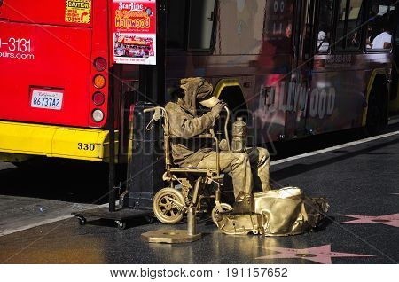 May 22 2017. Hollywood California. A man begging for money all covered in gold paint on the hollywood walk of fame in Los Angeles California near a starline tour bus.