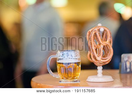 Closeup salted soft pretzels and beer on wooden background