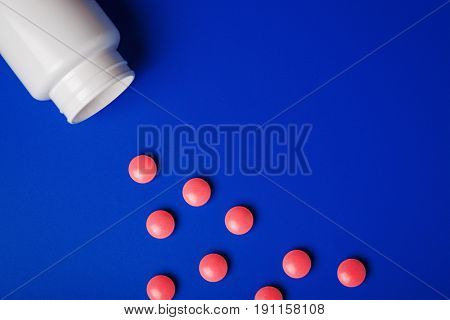 Medical Pills Round Shape And Bright Bottle Blue Background