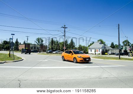 Grand Bend, Ontario, Canada - 02 July 2016: Orange Car Stopped At The Intersection For Priority