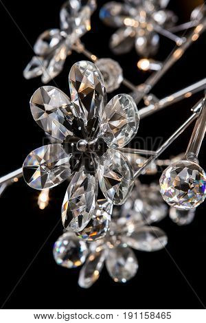 Modern high-tech chandelier with floral crystals isolated on black. Chandelier for interior of the living room, close-up
