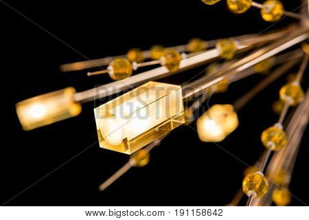 Modern high-tech chandelier with crystals isolated on black. Chandelier for interior of the living room, close-up