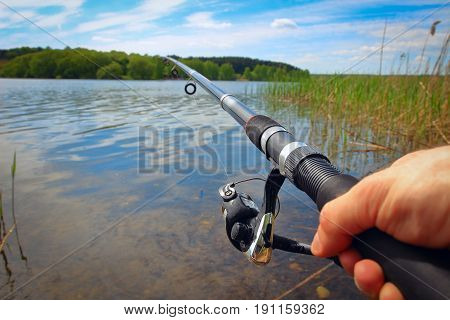 The fisherman is fishing on the lake with a bright sunny day in the summer. Fishing rod and hands of the fisherman over the lake water