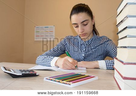 Education and school concept - Young girl sitting at desk at home doing homework looking at notebook