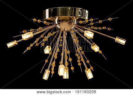 Modern high-tech chandelier with crystals isolated on black. Chandelier for interior of the living room