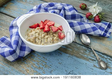 Oatmeal porridge with ripe strawberries on an old wooden surface