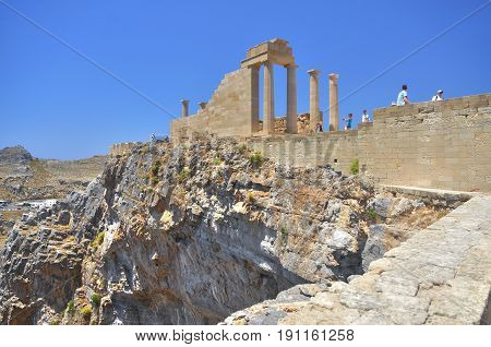 View on famous antique greek temple ruins on the rock on Greece island Rhodes in Lindos city and walking  tourists. Famous sightseeing places