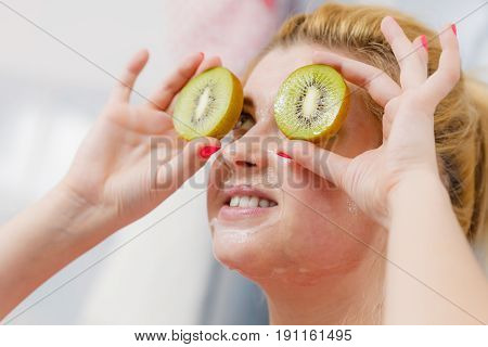 Woman Having Gel Mask On Face Holding Kiwi