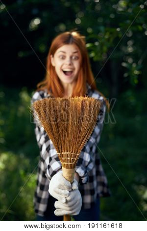 Woman with a broom, a woman looking at a broom in a vegetable garden.