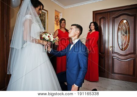 Groom Kneeling Down Kisses Hand Of A Bride And Gives Her A Beautiful Bouquet Of Roses.