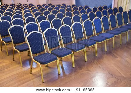 Rows of blue empty seats in unknown event hall