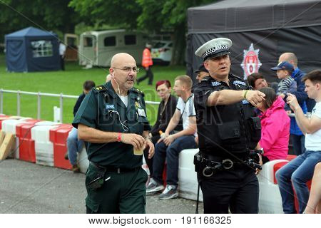 Beaulieu, Hampshire, Uk - May 29 2017: Police Officer Points Out An Incident To An Nhs Paramedic, Wh